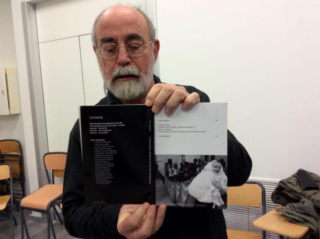 El profesor Bartolomé Ferrando, que ha viadado con sus acciones por todo el planeta, muestra el catálogo del Festival de Performance de Singapur / Laura Corcuera.